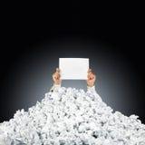 Persona bajo la pila arrugada de papeles con la ayuda si Foto de archivo
