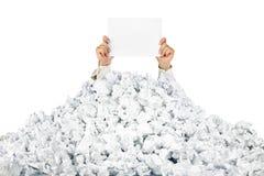 Persona bajo la pila arrugada de papeles con un espacio en blanco Imagen de archivo libre de regalías