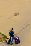Persona che cammina con i bagagli al parcheggio all'aperto Immagine Stock