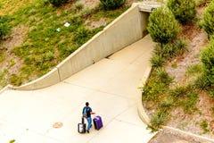 Persona che cammina con i bagagli al parcheggio all'aperto Immagini Stock