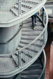Persona che cammina su una scala a chiocciola immagine stock