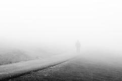 Persona che cammina sulla strada nebbiosa Immagine Stock