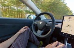 Persona che determina un nuovo modello 3 di Tesla nel modo del pilota automatico fotografia stock