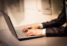 Persona che digita su un computer portatile moderno Immagini Stock