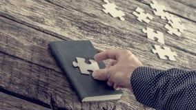 Persona che dispone un pezzo del puzzle su una copertina di libro Immagini Stock
