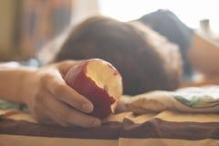 Persona che dorme e che si trova nel morso del abd del letto e mangiare mela fresca f fotografie stock