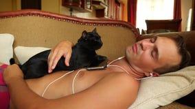 Persona che dorme nel giorno sullo strato con le cuffie dal telefono 4K Il movimento lento, il gatto nero si trova sul archivi video