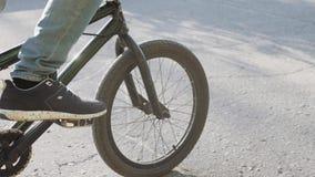 Persona che guida una bici all'aperto su un passaggio pedonale accanto ad un canale, alla fine sul punto di vista della sogliola  stock footage