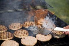 Persona che lancia gli hamburger durante il BBQ Immagini Stock Libere da Diritti