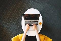Persona che lavora ad un computer portatile da spese generali fotografie stock libere da diritti