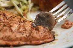 Persona che mangia salmone arrostito con pasta ed insalata su un piatto fotografia stock