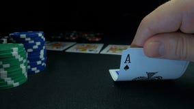 Persona che mostra la sua piattaforma al gioco del poker Il giocatore di carta controlla la sua mano, due assi, chip nel fondo su Fotografia Stock