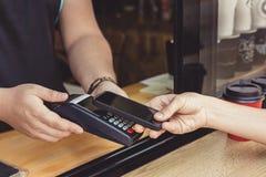 Persona che paga paga tramite lo smartphone facendo uso di NFC Fotografia Stock