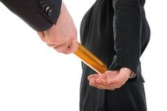 Persona che passa un bastone dorato del relè ad un'altra persona Immagini Stock