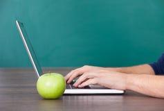 Persona che per mezzo del computer portatile oltre alla mela verde Fotografia Stock Libera da Diritti