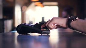 Persona che per mezzo del terminale della carta di credito per il pagamento senza fili con lo smartphone 4K video d archivio