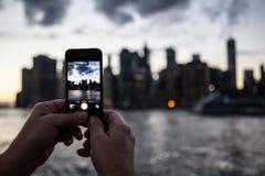 Persona che prende foto dell'orizzonte di Manhattan New York con il cellulare Ca Fotografie Stock