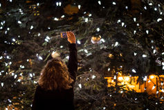 Persona che prende una foto di grande albero di Natale all'aperto alla notte Immagine Stock