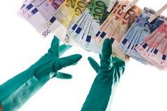 Persona che raggiunge per le euro note sulla corda da bucato, lavanderia dei soldi, primo piano Immagini Stock Libere da Diritti