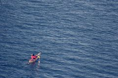 Persona che si esercita in canoa/kajak, in un mare meraviglioso Immagini Stock