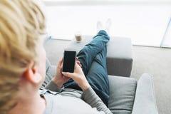 Persona che si rilassa e che per mezzo dello Smart Phone Fotografie Stock