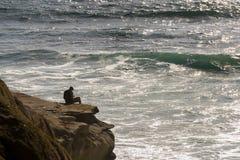 Persona che si siede sulle scogliere sopra l'oceano Immagini Stock