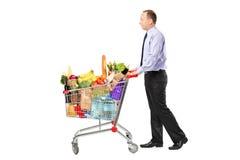 Persona che spinge un carrello di acquisto in pieno con le drogherie Fotografia Stock