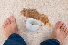 Persona che sta caffè vicino rovesciato su tappeto Fotografie Stock Libere da Diritti