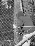 Persona che striscia con un'apertura del recinto con la mano che aderisce ad un filo di acciaio Immagine Stock