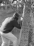 Persona che striscia con un'apertura del recinto con la mano che aderisce ad un filo di acciaio, in bianco e nero Fotografia Stock Libera da Diritti