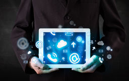 Persona che tiene una compressa con le icone ed i simboli blu di tecnologia Immagini Stock