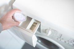 Persona che usando dosando aiuto per sporgere le labbra la polvere del detersivo di lavanderia nella lavatrice immagine stock