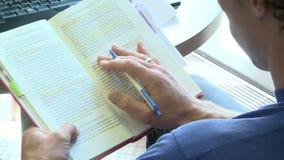 Persona che usando una penna per seguire la linea che sta leggendo in un libro stock footage
