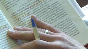Persona che usando una penna per seguire la linea che sta leggendo in un libro (2 di 2) stock footage