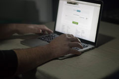 Persona che utilizza computer portatile nella stanza scura Lunatico, sinistro Immagini Stock
