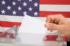Persona che vota davanti alla bandiera degli S.U.A. fotografia stock libera da diritti