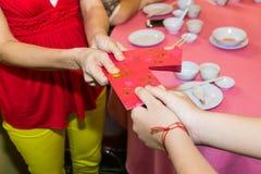 Persona china que da el paquete rojo con palabra del chino de la buena suerte Fotografía de archivo libre de regalías
