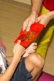 Persona china que da el paquete rojo con palabra del chino de la buena suerte Fotos de archivo libres de regalías