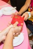Persona china que da el paquete rojo con palabra del chino de la buena suerte Fotos de archivo