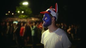 Persona con de la pintura de la cara la muchedumbre del fondo del partido de fútbol del watche entusiasta almacen de metraje de vídeo