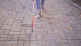 Persona con deficiencias visuales de la mujer joven con un bastón que camina alrededor de la ciudad metrajes