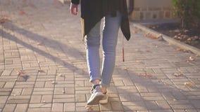 Persona con deficiencias visuales de la mujer joven con un bastón que camina alrededor del Sun City, vista posterior, MES lento metrajes