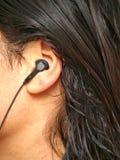 Persona con el enchufe de oído Imagen de archivo libre de regalías