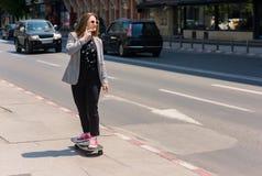 Persona con el monopatín que se coloca en la trayectoria en la ciudad Fotos de archivo