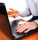 Persona con el ordenador portátil y la pizza Imágenes de archivo libres de regalías