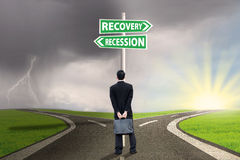 Persona con el poste indicador de las finanzas de la recesión y de la recuperación foto de archivo