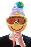 Persona con il cappello tricottato e passamontagna che nasconde il suo fronte dietro uno smiley Fotografia Stock Libera da Diritti