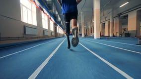 Persona con la gamba prostetica che corre su una pista, vista posteriore archivi video