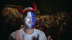Persona con la pintura en salto de la cara en placer de la victoria del partido almacen de video