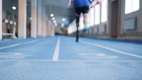 Persona con la prótesis biónica que corre en una pista especial, visión trasera almacen de metraje de vídeo